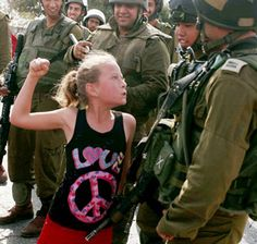 Standing up for peace ~ A Palestinian girl in a shirt decorated with the word 'love' & a peace sign faces off with Israeli soldiers during a Nov. 4, 2012 protest against the expansion of the nearby Jewish settlement of Halamish, in the West Bank village of Nabi Saleh.