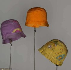 Three 1920s spring cloches: (1) lavender w/pink and yellow silk appliques, (2) mustard hand-painted w/orange, aqua, and green flowers and fruit, (3) tangerine silk, channel-quilted.