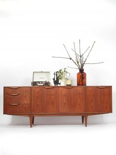 Teak mid-century modern design sideboard, with organically shaped handles and elegant legs with brass adjustable feet. This sideboard has on the leftside three drawers; two large and one regular size, in the middle a double cupboard with a shelf and on the rightside a drop down valve door which hides more space to put in bottles and a wide black sliding tray: to pour your drinks on.