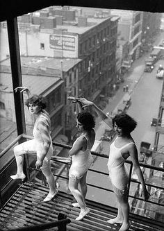 Heat Drives Follies Girls to Roof for Rehearsals. New York —  Pearl Eaton, Marie Wallace and Leonore Baron, members of the Ziegfeld  Follies Company, give pedestrians on the streets below a couple of  eyes-full while they go through their daily rehearsals on the roof of  the New Amsterdam Theater. The extreme heat made it necessary for the  girls to be put through their paces in the open. (1922)