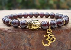 "Beautiful garnet bracelet, featuring a golden plated Om and a Buddha charm, perfect for your yoga class and meditation time. It is strung with stretch thread, beads size is 7.8 to 8mm.  Mother Earth has given us a wonderful gift, wearing gemstones and minerals can be of great benefit to us.  Garnet cleanses and re-energizes the chakras. It revitalizes, purifies and balances energy, bringing serenity or passion as appropriate. Garnets, the stone of ""Love & Commitment"", is a stone of romant..."