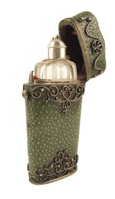 A late 18th century glass scent bottle, of slender form with feather cut edges and a silver coloured metal screw off cover with stopper, in a shagreen and silver coloured metal mounted hinged case, 3.5in (9cm) h.