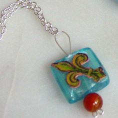 It may have started with a Fleur-de-lis, this one handcolored and embellished with orange agate (2011 inventory, sold)