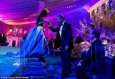 The President helps the First Lady off the stage after she thanked the White House chefs during the State Dinner for President Francois Hollande of France.