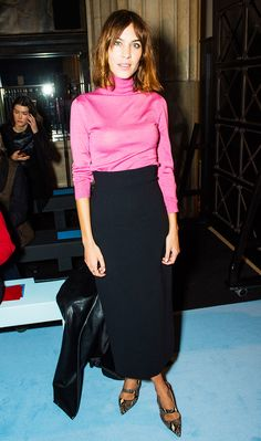 Alexa Chung in a pink turtleneck and high-waisted navy midi skirt