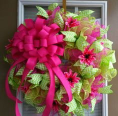 This wreath is made with approximately 90 of deco mesh ruffles in pink and green. It has coordinating green and white chevron ribbon, an