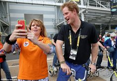 A right royal selfie: An excited Dutch fan has her photo taken with a beaming Prince Harry earlier today