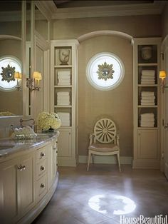 A Roman-Inspired Bathroom  In this neoclassical villa-inspired Texas house's master bath designed by J. Randall Powers, the rays of an antique starburst mirror hung in a round window are echoed in a contemporary wheelback armchair. The limestone floors, marble countertops, and alabaster urns reference ancient Roman materials.