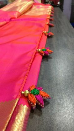 I love these embroidered saree pallu tassels - and it's a bit more of an unusual place to find embroidery too! Great combination of bright green, orange and pink in a floral leaf design. Saree Tassels Designs, Saree Kuchu Designs, Bridal Blouse Designs, Indian Dresses, Indian Outfits, Saree Border, Traditional Sarees, Saree Dress, Saree Styles
