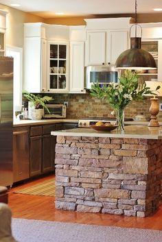 Stacked stone on island. Brick backsplash. Cabinets.