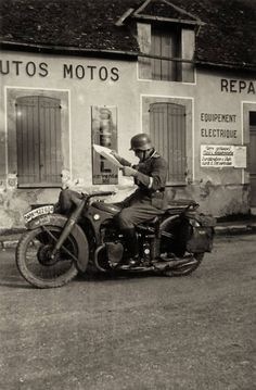 Motocyclist with his BMW and side car checking his map for directions in a small Italian town.