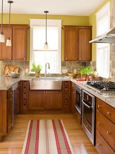 I like the warm colors used in this kitchen - the green walls, the stone back splash, and the dark orangish/red accents.