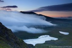 Sunset behind Brandon Mountain and the cloud of fog rolling over the mountain Ballysitteragh , Dingle , Co Kerry , Ireland