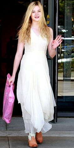 elle fanning with a long white dress and cowboy boots.