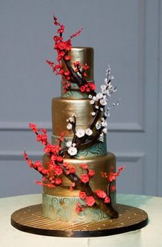 A #goldleaf cake with cherry tree blanches and flowers as cake embellishments