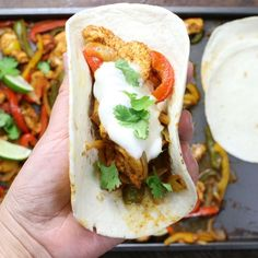 Baked Chicken Fajitas - here is a closeup photo of a chicken fajita fresh out of the oven in a flour tortilla and garnished with cilantro and sour cream
