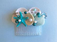 This beautiful comb of sea shells and pearls is amazing with an up-do, side-do or back-do and has been embellished with a variety of lovely treasures from the sea including sea shells in white and ivory, a knobby sea star painted turquoise and a clam shell painted aqua. Faux pearls in teal, turquoise, aqua and ivory have been added for a bit of bling along with a small silver sea star.  The comb itself is 2.75 inches wide and is available in clear plastic, black plastic, brown plastic, nude…