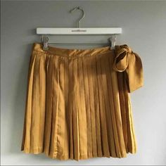 Gap mustard yellow silk pleated skirt BNWOT. Never worn and in excellent condition. Size 6. Bow ties on the side. Zip closure. GAP Skirts Mini
