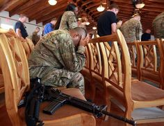 An American Soldier holds his head during prayers on Sept. 11, 2011 at Bagram Air Field, Afghanistan. Ten years after the 9/11 attacks in the United States and after almost a decade war in Afghanistan, American soldiers gathered for church services in prayer and solemn observence of the tragic day. (John Moore/Getty Images)
