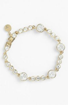 "Regimented Swarovski crystals add neat, watery sparkle to a slim bracelet tipped with a logo charm.  Approx. length: 7 1/2"". Approx. crystal diameter: largest 3/8"". Fold-over clasp closure. Goldtone or silvertone plate/Swarovski crystal. By Givenchy"
