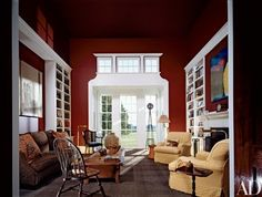 """Barkley calls the library a """"perfect idealized cube. The moldings are lyrical and as fancy as we get."""" An oil by Susan Sales hangs above the fireplace. At left is a work by Suki Bergeron. Sofa from Donghia. Stark carpet 