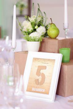 """Neben der klassischen Tischnummer, die hier passend zum Hochzeitsmotto """"Umzug"""" aus Pappe gefertigt und auf eine Landkarte aufgebracht ist, wurde jeder Tisch nach einem Ort benannt, an dem das Brautpaar gemeinsam gelebt hat.  Eine Dekoration von www.tischleinschmueckdich.de"""
