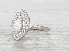 Antique Art Deco engagement ring made in platinum and centered with an EGL certified .85 carat marquise cut diamond. Accented with a halo of old European cut diamonds. Circa 1920