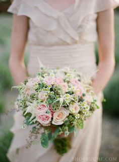 A rich bridal bouquet of wildflowers and roses.