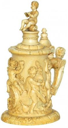 10 ½  Carved Ivory tankard. Detailed carvings of frolicking cherubs. Figural winged cupid handle. Figural cherub plays flute while sitting on a shell finial. Early to mid 19th century. Great quality
