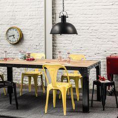 Dans une salle à manger au style industriel, les établis deviennent des tables de salle à manger robustes, avec leur armature acier et leur plateau en bois, les tabourets trouvent place autour de la table ou face au bureau, les chaises sont revisitées avec une touche de couleur vive, un peu vieillie pour plus d'authenticité.
