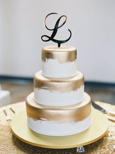 White and gold polished three tier initial topped wedding cake: http://www.stylemepretty.com/florida-weddings/2016/10/13/pastel-blogger-wedding/ Photography: Gianny Campos - http://www.giannycampos.com/