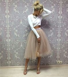 Fashionable outfit with white crop top and beige midi tulle skirt