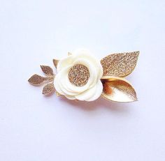 This ivory felt flower with gold & gold glittered leaves arrive on your choice of a nude nylon headband (one size fits most) or a single prong alligator hair clip (lined with felt under top inside prong). Measuring at 1.5 in diameter (excluding leaves) and about 3.25 in length
