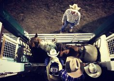 A shot from above of a bronc rider on a horse behind a gate