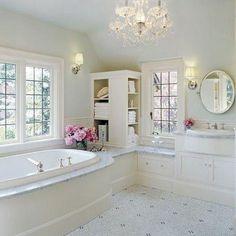 Nice huge bathroom. Love the windows, tub, mirror, chandi....country it up a bit more.