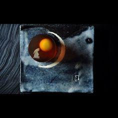 """一日一菓 「月見兎」 錦玉羹 製 wagashi of the day """"Rabbit looking at the moon"""" 本日は「月見兎」です。 今年は御彼岸明けすぐに十五夜です。 全国区では御月見と言えば「団子」が主流かと思いますが、関東では御月見に団子の他、御饅頭を食べる風習があります。 私の住んでいる「横須賀」では、むしろ御饅頭の方が主流です。 この御月見という文化も元々中国に起源する文化です。 御月見当日の前後二日間を、前/待宵(まつよい)後/十六夜(いざよい)と言い、同じく月を愛でます。 そんな御月見をテーマにした上生菓子です。 紅茶錦玉羹 にて夜空を表し、レモン餡にて「月」を表しました。 なので、 お召し頂いた時のお味はまさに「レモンティー」です。 月を愛で見るウサギは白羊羹で描いました。 御月見に限らず 月を見るのが好きです。 夏の少しだけ涼やかな夜空が好きです。 紫色した月を見たことがあります。 何つながりだかよくわかりませんが、 銀河鉄道の夜とか、 銀色夏生とか好きです。 そこに広がった夜空によせて。 なんか月を見て、そぉ思いました。 #和菓子..."""