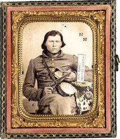 Thomas Isaiah Booker in Confederate uniform with Colt navy revolver, book, tin drum canteen, and sign reading Jeff Davis and the South!    Summary: Photo shows identified soldier from Louisiana from either Co. D, 8th Louisiana Cavalry Regiment; Co. B, 28th Louisiana Infantry Regiment, or Co. B, 29th Louisiana Infantry Regiment.    Soldier identification from great granddaughter Suella Booker Cooper (November 2012)