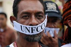 Gagged    An Indigenous man with his mouth covered by a UNFCCC (United Nations Framework Convention on Climate Change) gag during a protest at the climate talks held in Bali, Indonesia in 2007.   The protest concerned the exclusion of Indigenous Peoples from the official negotiations even though the UNFCCC was developing plans to use their lands to provide resources and carbon offsets to supposedly address climate change.