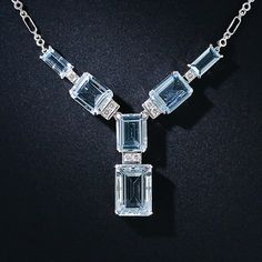 Six shimmering pastel-blue aquamarines are artfully arrayed in a modern rendition of a classic geometric Art Deco design and enlivened with small diamond sparklers in this chic and sophisticated necklace.