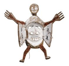 This transformation mask depicts a human figure with outspread arms and legs. The limbs are also mouths, painted red inside and studded with peg teeth. A semi-human face is carved on the outside of the doors, which opened dramatically when a dancer pulled on the sinew cords. The face revealed inside is the yua, or inner person, of the creature. It has goggled eyes and a mustache. Two seals are painted inside one door, two caribou on the other. The mask originally had feathers inserted around...