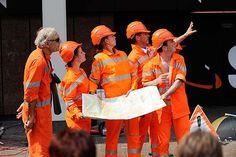"""""""Carambole"""" - Fünf Bauarbeiter in orange neonfarbenen Anzügen mit ungewohnt skurriler und witziger Körpersprache."""