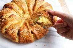 Brunchbrood Ingrediënten voor 1 brunchbrood (12 stukjes): 1 rol croissantdeeg voor 6 grote croissants 12 plakken bacon 6 + 1 eieren 1 eetlepel crème fraîche 2 dunne bosuitjes 1 flinke theelepel chili flakes 100 gram pittige geraspte kaas 1 theelepel sesamzaadjes