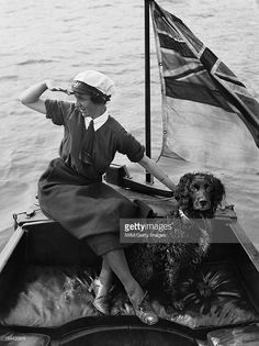 Women In Uniform During The First World War: The Women's Royal Naval Service, Southwick, 1918, A striking portrait of Mrs Gladys Barnes, a WRNS motor boat driver, as she sits at the tiller of her boat, the 'BALMACAAN', with her spaniel dog beside her in Southwick, Sussex. Her right arm is raised to her face, as if in salute, to shield her eyes from the sun, June 1918.