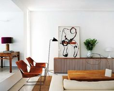 white walls, chairs, floor lamp, sideboard