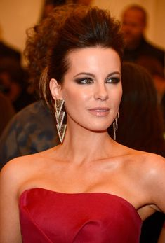 A high pompadour, smudged smoky eye, and shining lip gloss made up Kate Beckinsales beauty look for the night. #MetGala