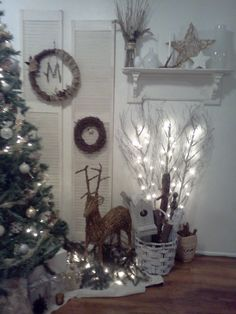 White Christmas décor:  Old shutters, light up branches, reindeer, birdhouse, stars and wreaths