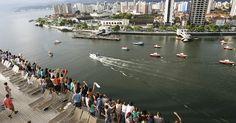 Turistas acenam de dentro de navio de passageiros para parentes na Ponta da Praia, em Santos