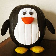 """Dress your pumpkin up in a penguin suit to add a little class to your decor.                 Penguin How-Tos 1. Draw an outline of a peanut shape on the front of your pumpkin using a pencil. 2. Paint the area inside the peanut shape outline white and paint the rest of the pumpkin black. 3. Cut two semi-circles of orange felt for the beak (about 3"""" wide for an average sized pumpkin), four teardrop shapes in black for the wings (about 6"""" long), and four semi-circles in yellow for the feet…"""