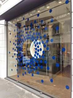 Blue dots lifted from Colette's iconic two-dot logo surround a white circular neon-lit tray heroing a pair of limited edition Stan Smith trainers, and disperse towards the outer edges of the window, mimicking the dots on the toe box. Window Display Design, Shop Window Displays, Store Displays, Retail Windows, Store Windows, Visual Merchandising, Wayfinding Signage, Store Signage, Window Signage