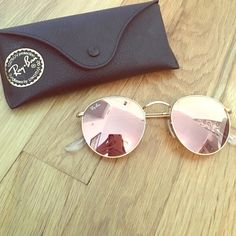 """Artista gold copper"" colored sunglasses by Ray Ban. They reflect like a mirror and are a very pretty copper/ rose gold color. 100% UV protection, wire rimmed round sunglasses. There are nose pads as well."